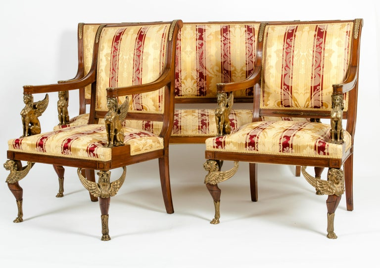 Spectacular late 19th century French Empire style handcrafted three piece gilt bronze salon suite. One upholstered sofa & one pair of armchairs. The armchairs are set on four straight mahogany legs, the front two of which are set on gilt bronze paw