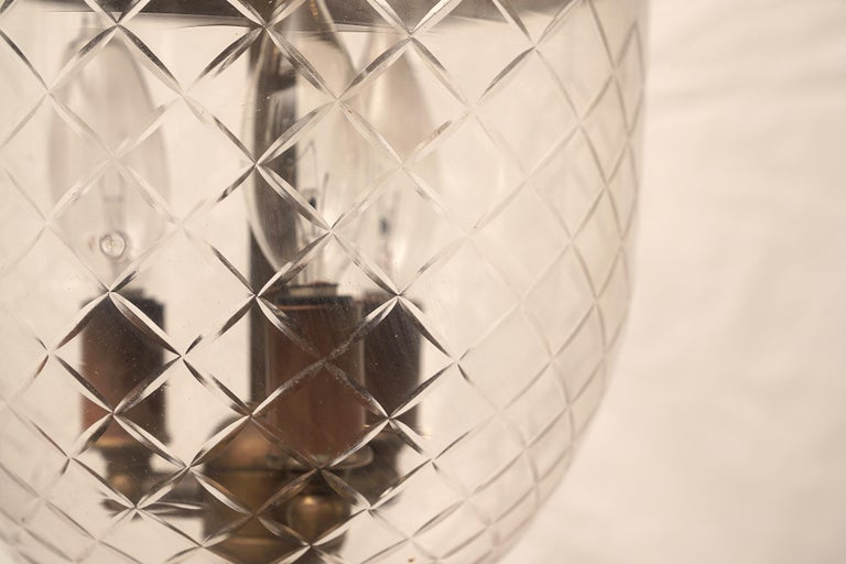 Handblown glass bell jar lantern with a prismatic diamond design etching, complete with the smoke bell lid. Originally used with candles, the lid kept the flame from scorching the ceiling. Embossed brass band with griffin hooks with natural patina
