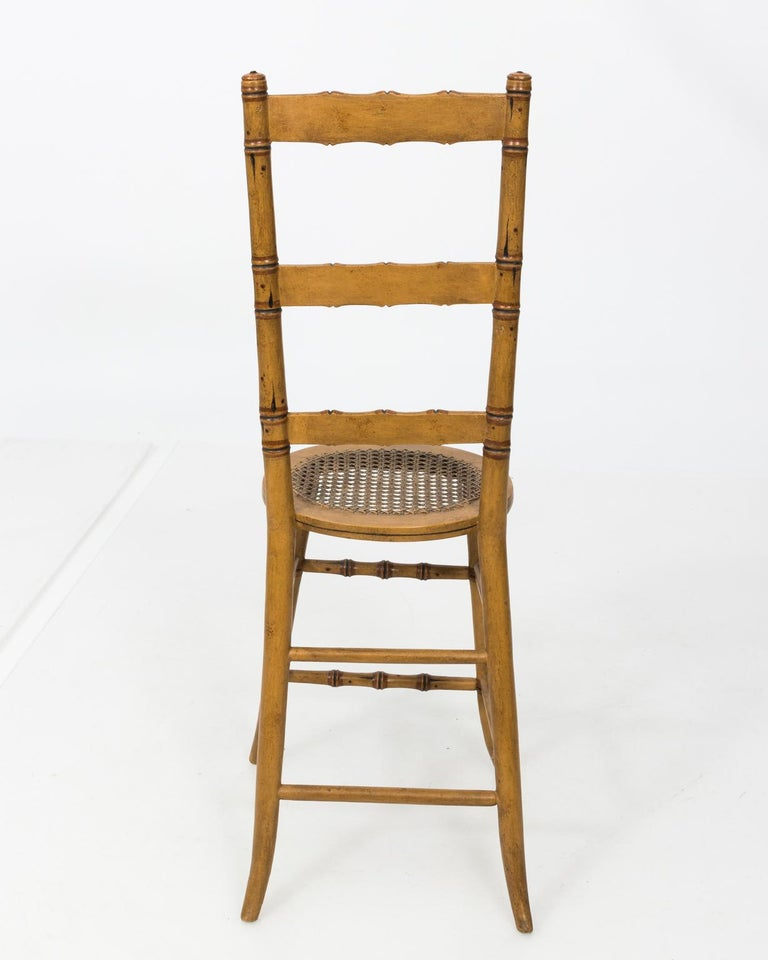 Late 19th century faux bamboo child's chair with ladder back and cane woven seat.