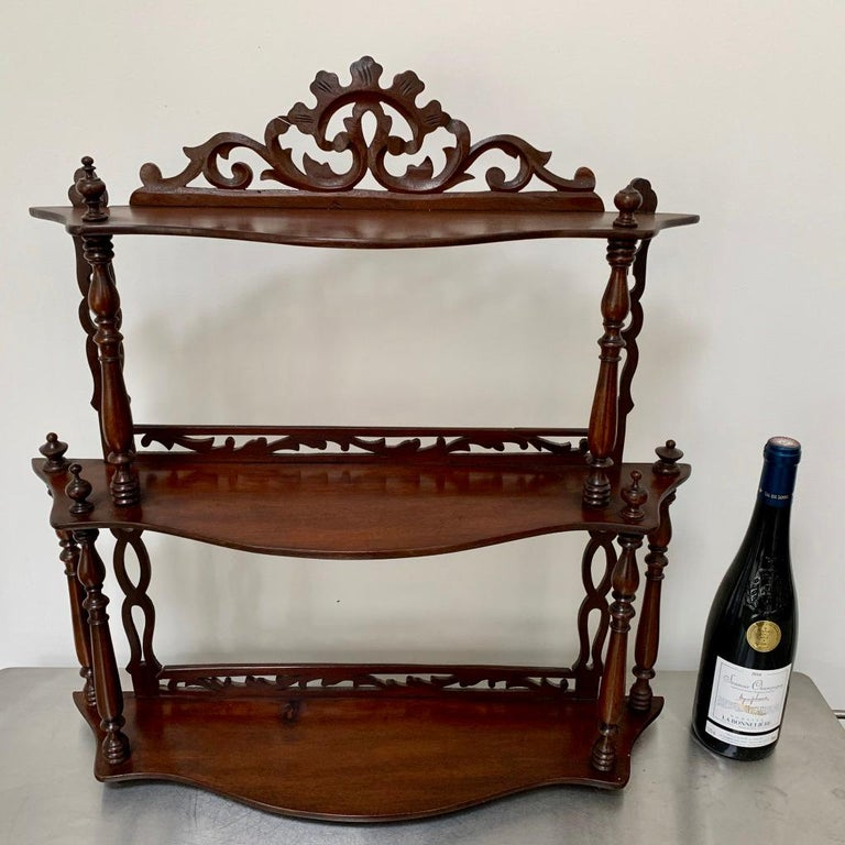 Nice quality and decorative set of freestanding or hanging shelves, made in solid mahogany with 3 shelves. This set of shelves has a carved cartouche to the top shelf, fretwork carving for the vertical supports and shelf backs, with fine turned