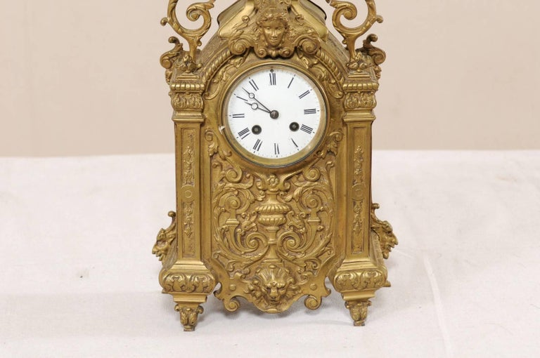 An ornately decorated French brass mantel clock from the turn of the 19th and 20th century. This antique French clock is exquisitely decorated on all sides, it has an overall scrolling foliage, acanthus leaf, and urn motif, with a pair of winged