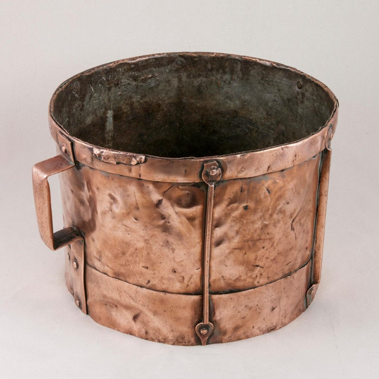 This late 19th century, French copper grain measure features copper riveted handles and copper riveted supports around its cylindrical form. Its bottom is concave which would have allowed for carrying it on one's head when transporting grain or even