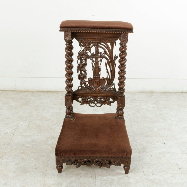This French hand-carved oak prayer chair, or prie-dieu, in French, features double barley twist columns at the back that support the armrest. Rosettes adorn the die joints at the top and bottom of the columns. The back displays an intricately