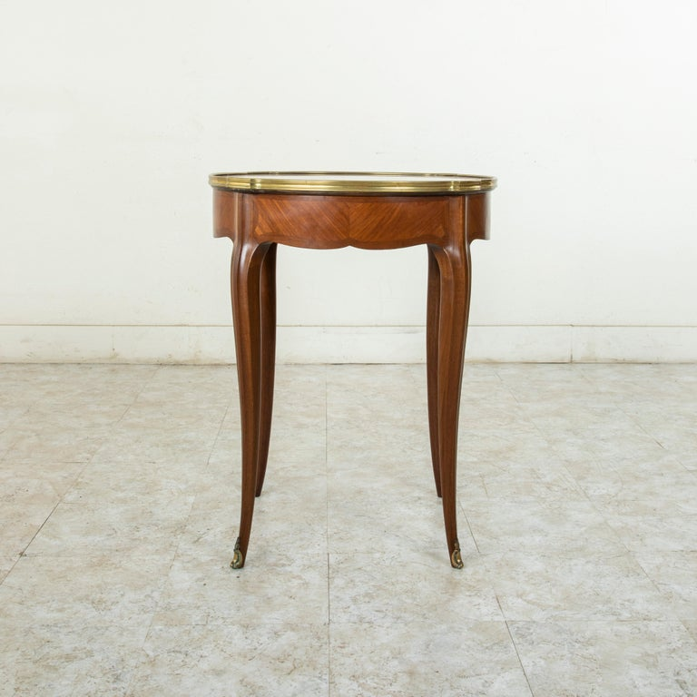 This French Louis XV style gueridon side table from the late 19th century features a book matched walnut fascade and a fleur de pecher marble top. Bronze trim surrounds the marble top, and its curved cabriolet legs are finished with bronze sabots,