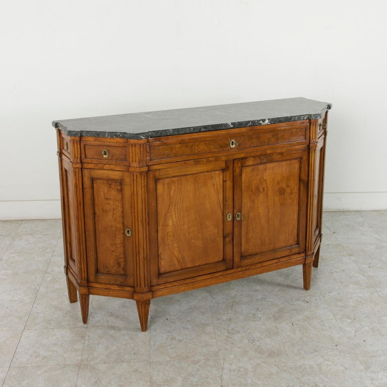 Found in Paris, France, this late 19th century Louis XVI style enfilade, sideboard, or buffet features a rare five-sided ashwood facade with a beveled Saint Anne marble top. The piece has Classic Louis XVI fluted corners and rests on tapered fluted