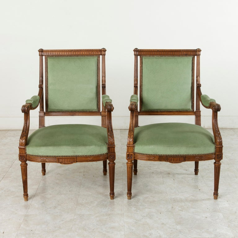 This pair of late 19th century French Louis XVI style armchairs is constructed of solid walnut with beautifully hand carved detailing that includes Classic motifs of beading, crossed ribbon, and rosettes at the die joints. Acanthus leaves adorn the