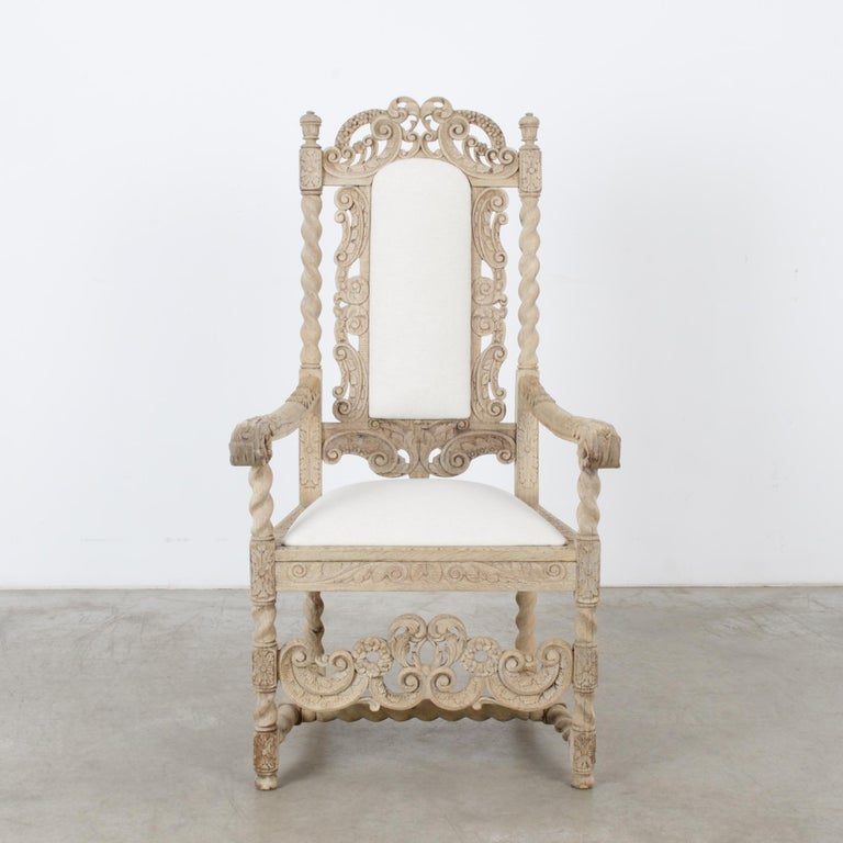 A bleached oak armchair with an upholstered seat and backrest from France, circa 1880s. The throne-like frame is embellished with elaborate carving. Twisted columns, leaves, flowers and berries abound among a lively interplay of scrolls. The light,