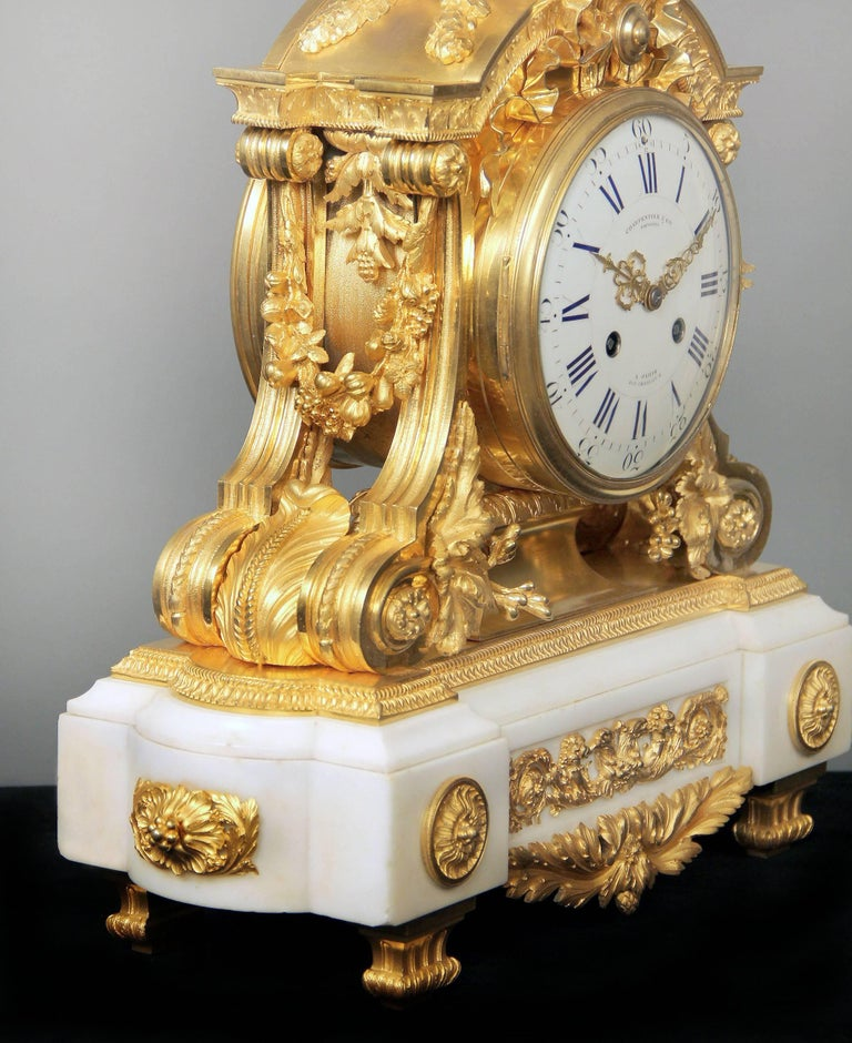 A fantastic quality late 19th century gilt bronze mounted white marble mantle clock.  By Charpentier & Compagnie.  An urn with laurel leaves above a tied bow, the sides with swags of flowers and fruit, the marble base mounted with a double eagle