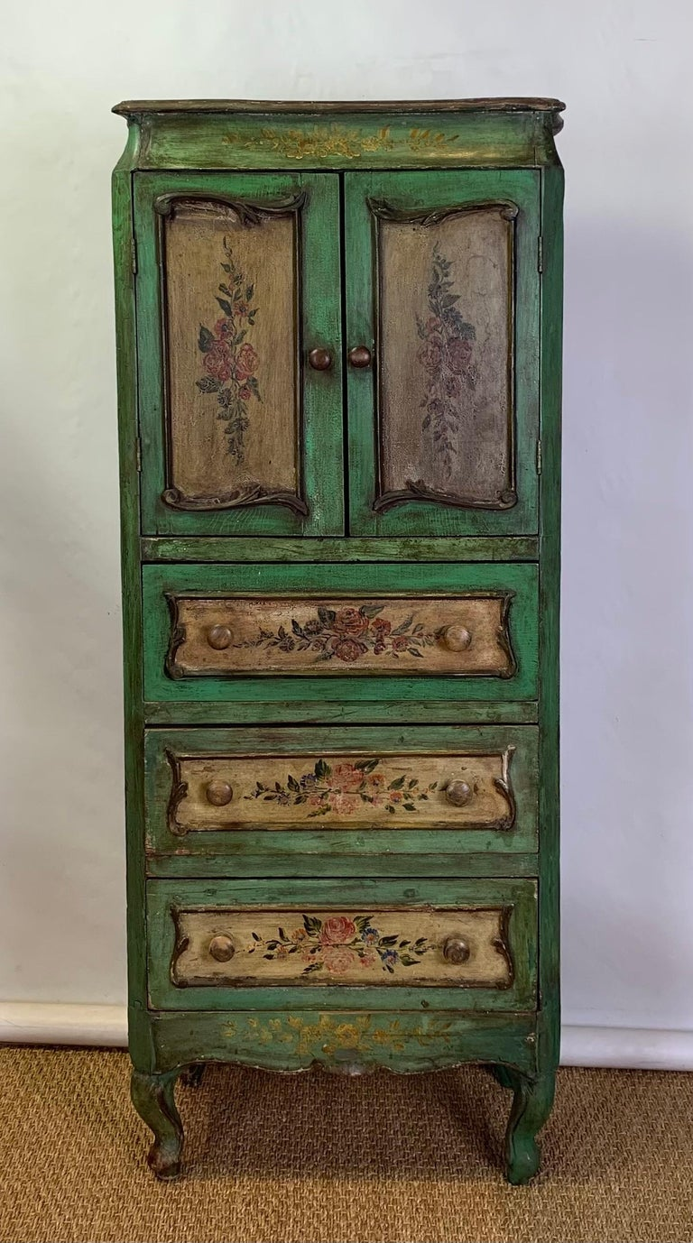 A colorfully painted and decorated late 19th century Italian semanier or lingerie cabinet having two cabinet doors above three drawers resting on cabriole legs.