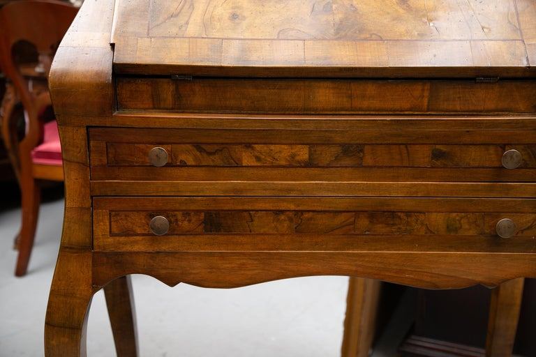 This is a mellow Italian burl walnut desk with a drop front top over two long graduated drawers and supported by graceful curved legs, 20th century.