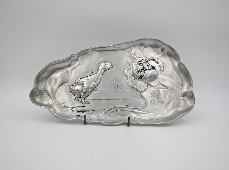 An antique Kayserzinn footed tray in highly polished pewter from J. P. Kayser & Sohn AG of Krefeld, Germany, dating circa 1895. The tray has a reflective silver glow and is decorated in relief with natural motifs and whiplash lines characteristic of