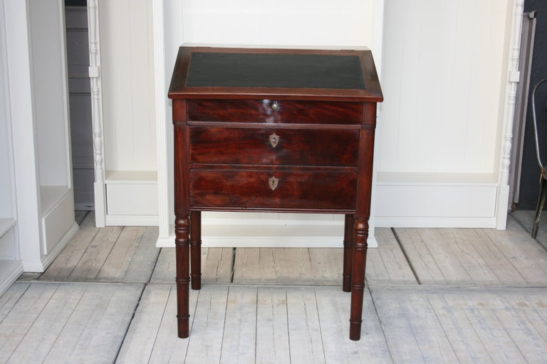 An antique late 19th century lectern made of mahogany and burl veneer. Standing on 4 high turned legs with 3 drawers and a beveled writing flap with leather. A very small secret door on the right side (see pictures), which was probably originally