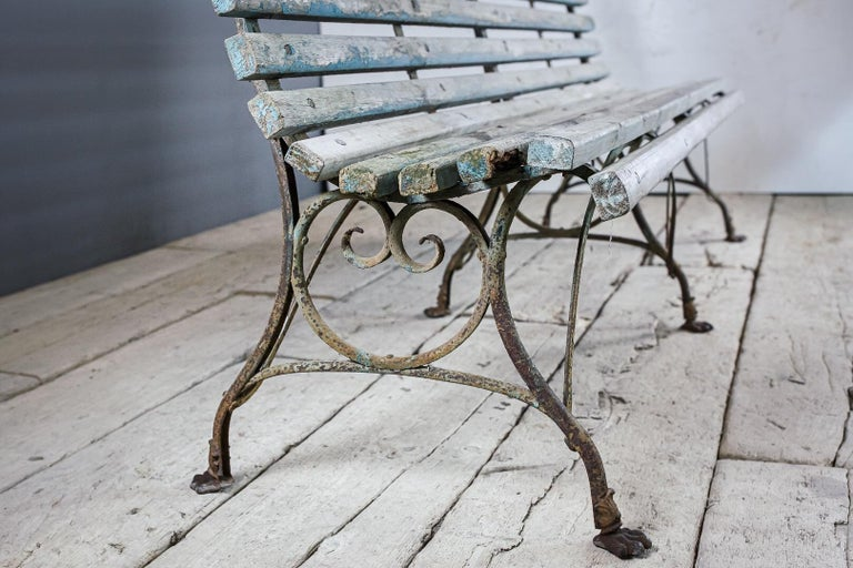 Late 19th century large Arras garden or conservatory bench, sculptural wrought and cast iron 6 legged base. Earlier lion paw feet model. Unusual wood slat model, solid and sturdy with historic paint. Wonderfully sculptural, dry original surface.