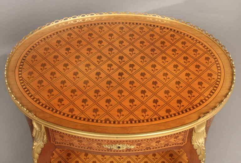 A beautiful late 19th century Louis XV style gilt bronze-mounted marquetry lamp table  The two-tier table with a pierced gallery inlaid floral marquetry top above a single drawer.