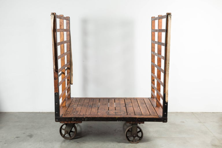 Late 19th century substantial luggage cart from a Midwestern United States train station. Cart moves on four cast iron casters. Wood slats with riveted and woven fabric straps. Stencilled with cart number and station info. Found at Union Station in