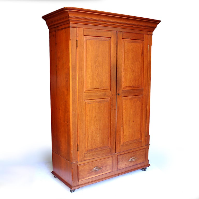 Wonderful 1880s neoclassical wardrobe with many unique features!  Features include:  - Solid cherrywood construction - Swing-out hangers - Original double-wheel steel casters - Knock-down/collapsible design - Secret compartment hidden under
