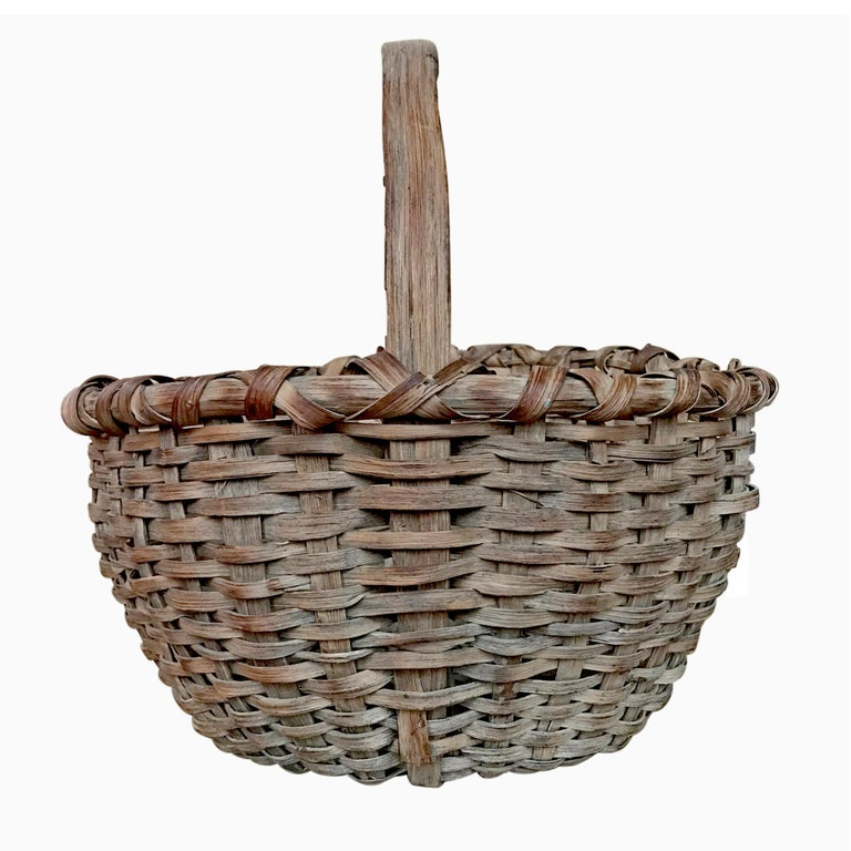 A late 19th century American handwoven oak splint gathering basket with a single bentwood handle, thin splints, and a wonderful patina. Found in Connecticut.