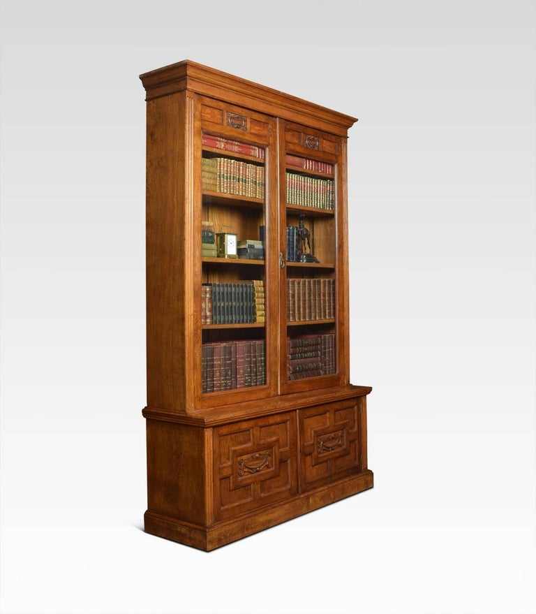 Solid oak two-door bookcase, the projecting cornice, above carved freeze leading down two a large pair of glazed doors. Opening to reveal four adjustable shelves. The base fitted with two geometric carved paneled doors opening to reveal single fixed