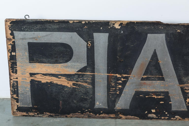 Late 19th century American Folk ArtPianos trade sign. 8 feet long. Very graphic time worn art piece. Looks great on a stark white wall. Black with grey letters on one side and black with gold letters on the reverse. Gold lettering is very faded.