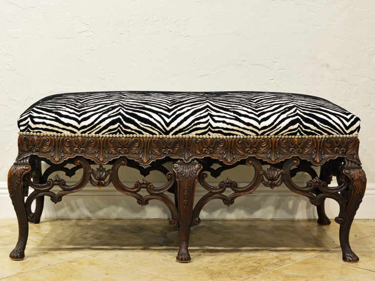 Resting on 6 carved legs connected by intricately carved open work in the shape of scrolls and leaf work this 19th century French Louis XV style this very chic bench features recent upholstery and silver finish nail head trim. The high end fabric is