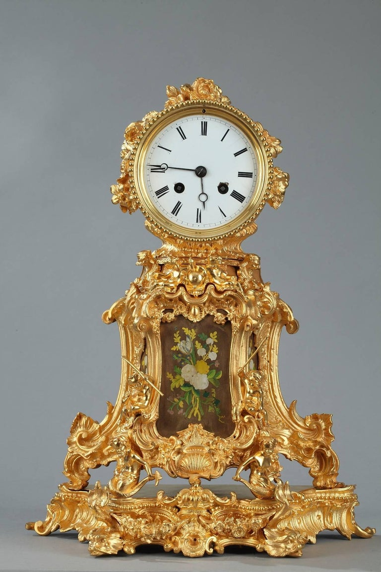 Mantel clock in gilt and sculpted bronze featuring abundant Rocaille motifs such as rinceaux, shells, distressed leaves, and scrollwork. Putti engaged in activities such as reading, fishing, or playing music complete the decor that is characteristic