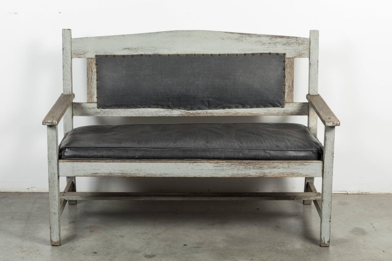 Great looking late 19th century railroad station bench found in the mid-west. Original grey paint on wood surface and very nicely aged leather seat and seat back. Solid and sturdy.