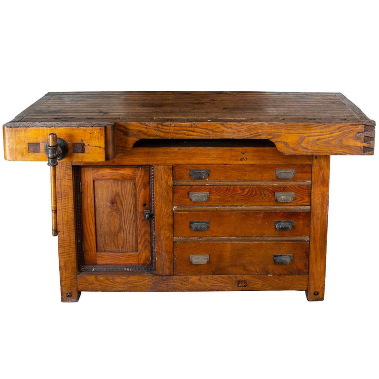 This beautiful solid ash and rock maple workbench is an excellent piece of late 19th century craftsmanship. The fully functional vise grip has a hand carved solid ash handle. The cabinetry is adorned with an egg and dart border and each drawer is