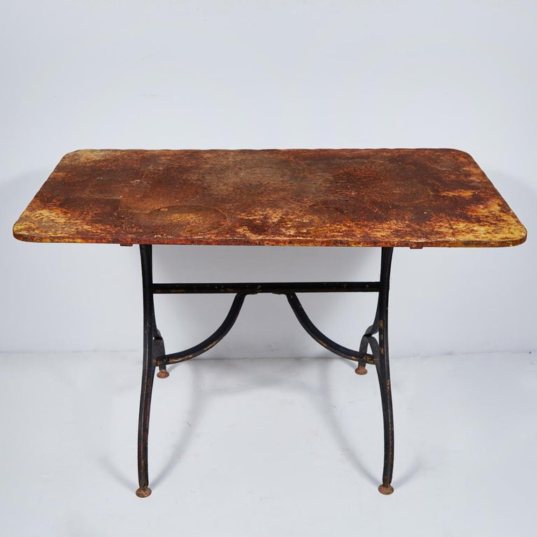 Late 19th century yellow garden table with natural patina on a iron trestle base from France.
