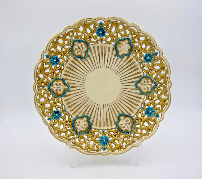 An antique ornamental cabinet plate / dish from Zsolnay Pecs of Hungary, dating circa 1880s. The faience plate is a fine example of late 19th century Victorian Eclecticism, featuring aspects of Zsolnay's Turko-Hungarian decor with gilt, gold, and