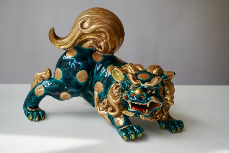A painted Japanese porcelain sculpture representing the Foo dog. Features include incredible detail and expression with beautiful green and gold color. Fu dog, foo dog or lion dog, or Chinese temple lion. Foo (Fu) means prosperity and good fortune