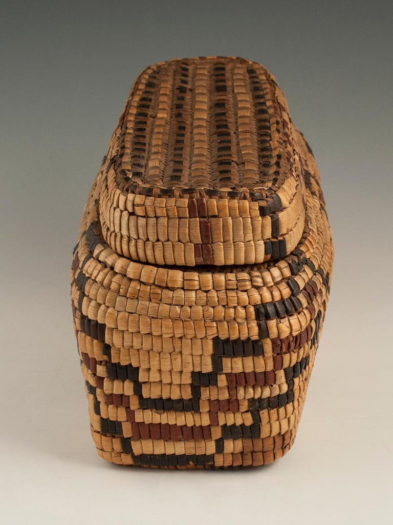 Late 19th-early 20th century tribal Native American Columbia river basket.  A graphic, fully imbricated polychrome reed and cedar bark lidded basket, unique to the Native American tribes of the Columbia River Plateau in the Pacific Northwest.