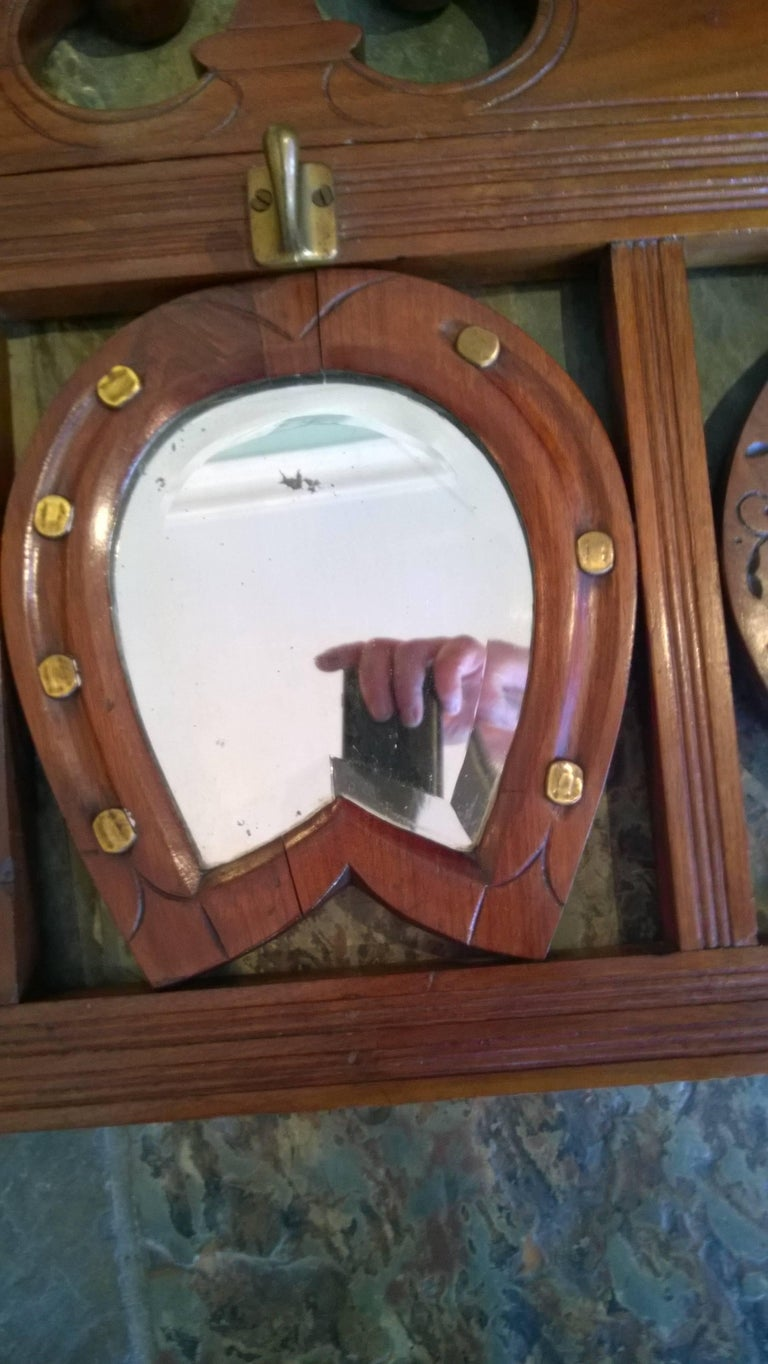 Late 19th century walnut mirror hall stand cum hat and coat rack of equestrian theme with horseshoe central mirror flanked by two fan shaped mirrors surrounded by six hooks 44