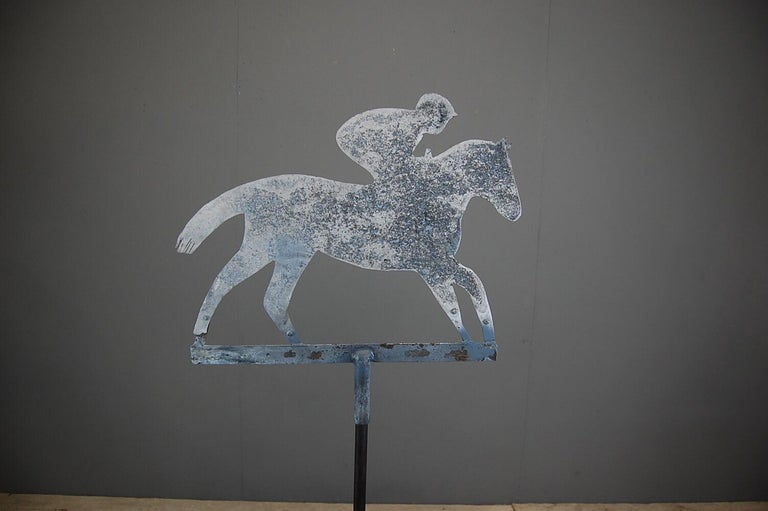 Horse and jockey sheet metal silhouette weathervane. Unusual patination and weathering. Mounted on a later stand for display. Presumably from a riding stables or livery yard. Measurement includes stand