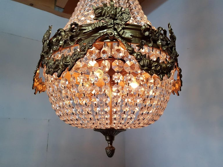 Heavy 8 lights crystal chandelier in Louis XVI style with gold colored metal frame decorated with garlands and bows in very good condition, late 20th century.