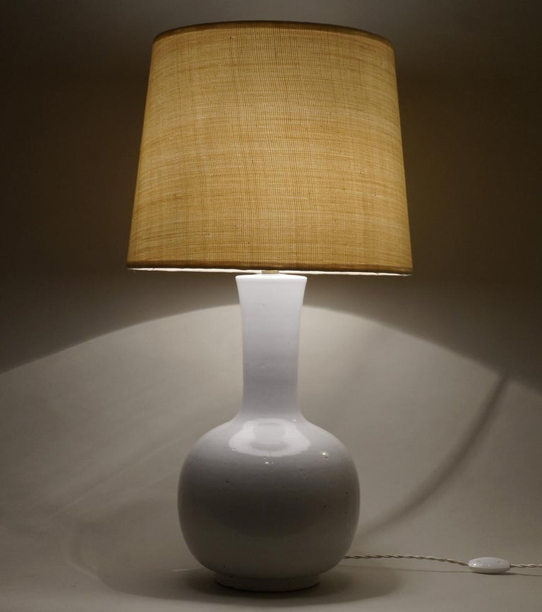 White enameled ceramic table lamp, custom-made fabric lampshade in abaca  rewired with twisted silk cord.  Measures: Ceramic body height 40 cm – 15.7 in. Height with lampshade 69 cm - 27.2 in.