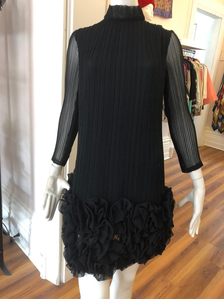 Wonderful permanent pleat dress, with elaborate ruching at bottom in a quasi floral pattern. The dress has a high neckline; see through sleeves and is lined. Closure is by way of a hidden centre back zipper. This is a truly magnificent piece in