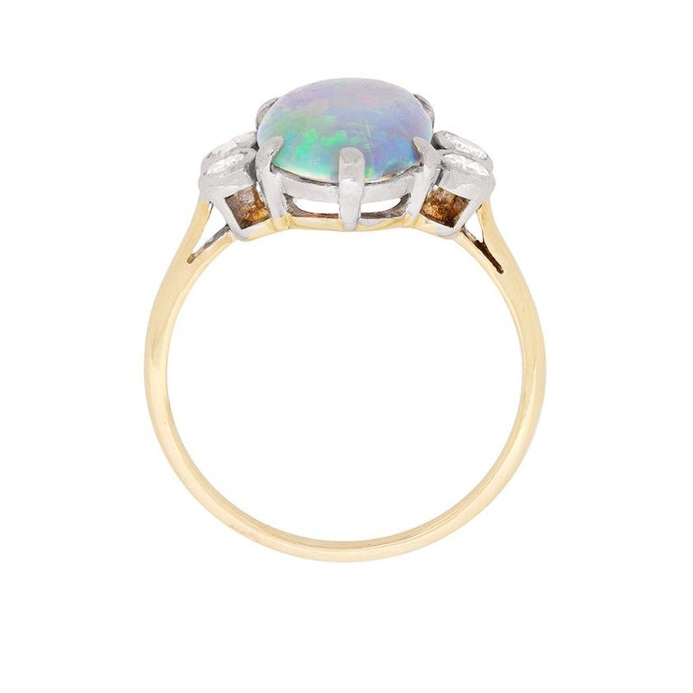 This unique ring features a stunning black opal, one of the most popular semi-precious gemstones, which weighs 1.60 carat. Black opals are mined in Australia and have stronger dark hues throughout the gemstone. It is a cabochon cut stone, which is