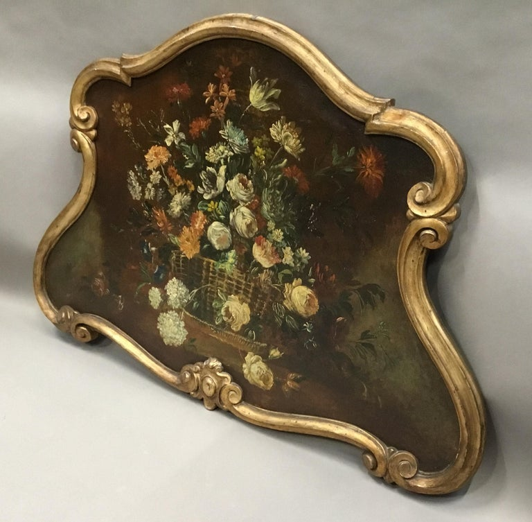 Late 18th century Dutch still life oil painting of unusual cartouche shape; the oil painting on canvas of an oval basket, overflowing with colorful flowers, housed in its original carved, scrollwork, giltwood frame. Very good original