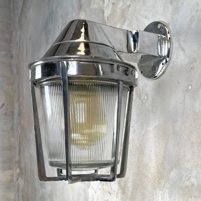A large vintage cast aluminum sconce with prismatic glass shade and cage. These aluminum wall light fixtures are made by Appleton Electric USA with outstanding build quality and materials. The main body is cast aluminum, the cage mechanically