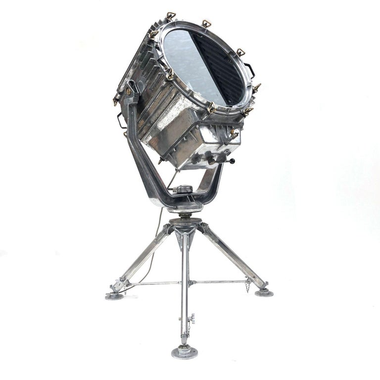 A reclaimed retro industrial aluminium marine searchlight paired with a British Telecom satellite tripod to create an exceptional large bespoke floor lamp.  The searchlight was originally used to illuminate the banks of the Suez Canal. It was