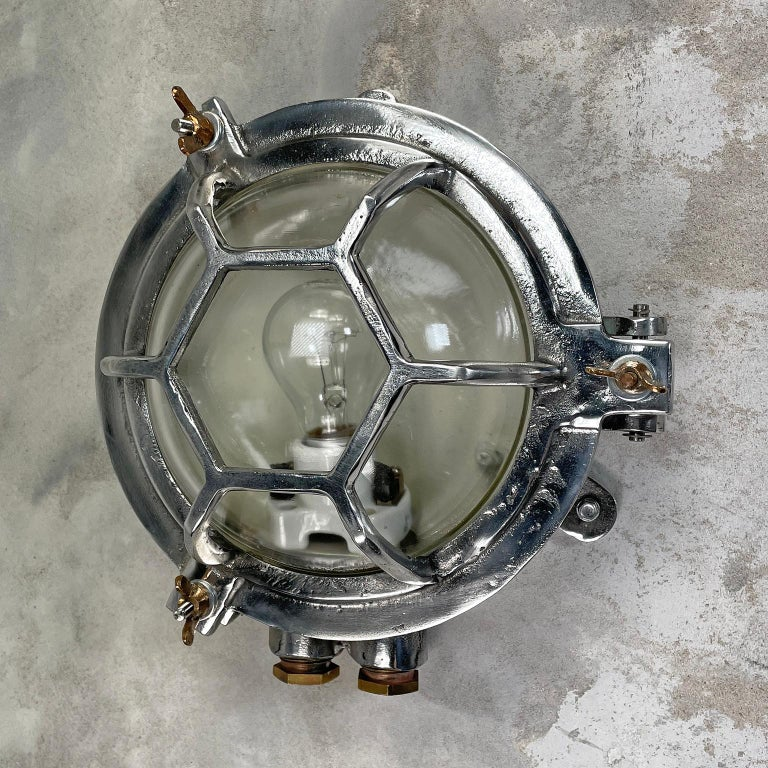 A vintage industrial aluminium outdoor circular bulkhead wall light with a hexagonal target cage and clear glass.   Originally marine lighting, this type of aluminium circular bulkhead is found on ship passageways. Professionally restored and