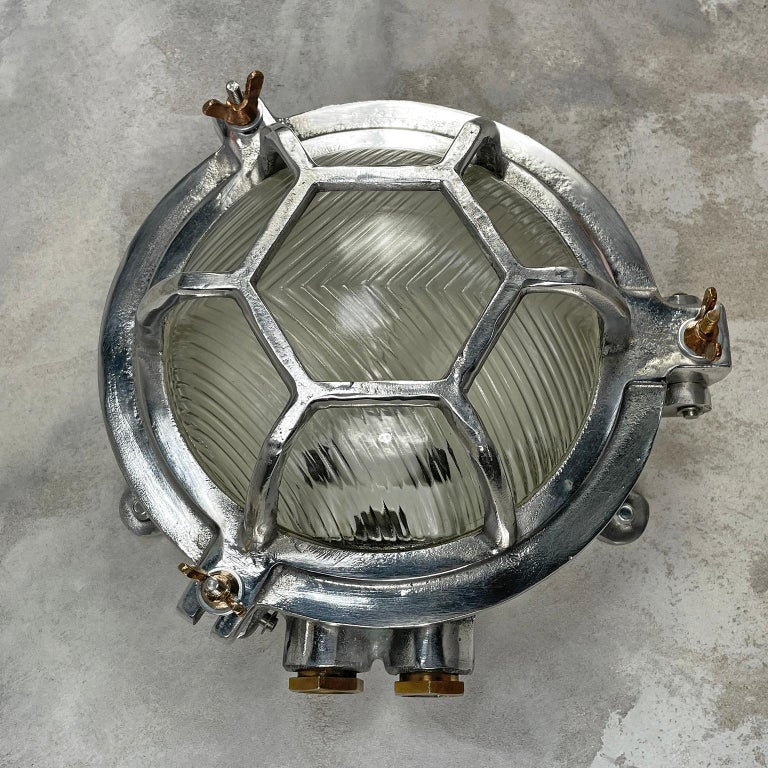 A vintage industrial aluminium outdoor circular bulkhead wall light with a hexagonal target cage and prismatic / reeded glass.   Originally marine lighting, this type of aluminium circular bulkhead is found on ship passageways. Professionally