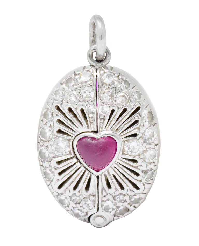 Charm designed as oval centering a ruby cabochon heart surrounded by pierced radiated line motif emulating the Sacred Heart of Jesus  Accented throughout by bead set old European and single cut diamonds weighing approximately  Opens on a hinge to