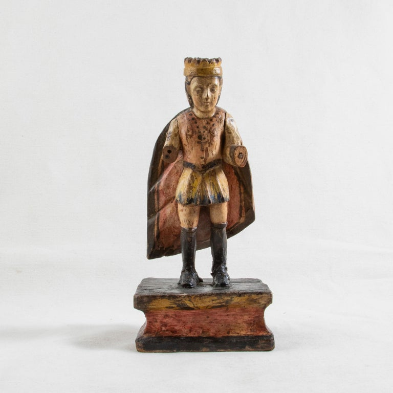This late 18th century hand carved polychrome sculpture from Spain features the figure of a king wearing a crown and cape. The king stands in knee high boots and wears a short tunic and a cross hanging from a chain around his neck. His arms are hand