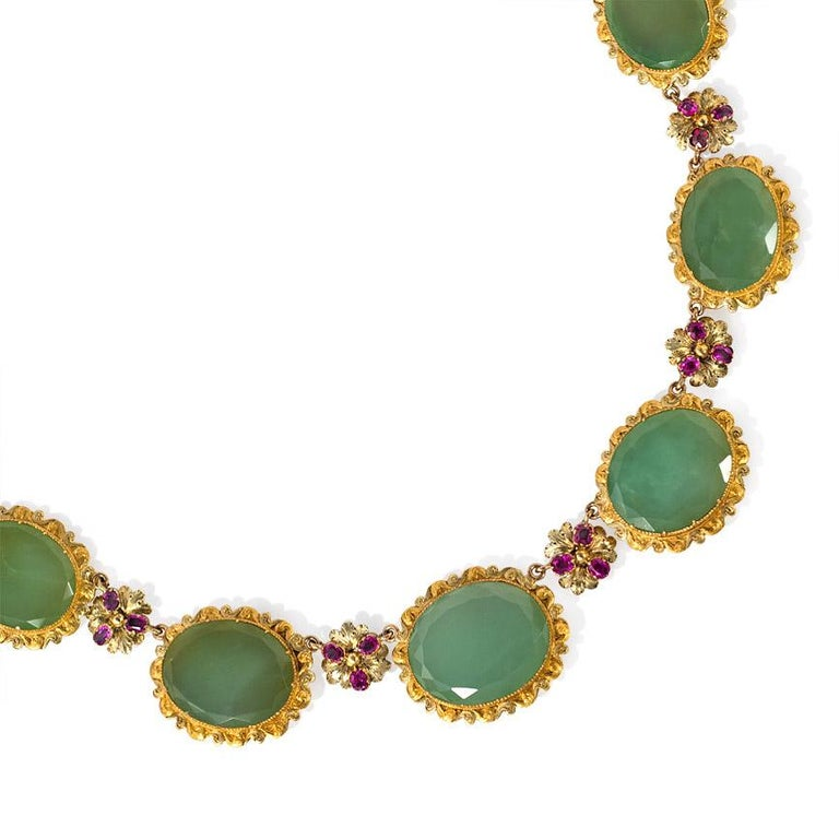 An antique late Georgian period necklace comprised of graduated oval chrysoprase set in foliate surrounds with alternating trefoil ruby florets, in 18k gold. A similar necklace appears in The Frick Collection's portrait of Comtesse Daru, painted by