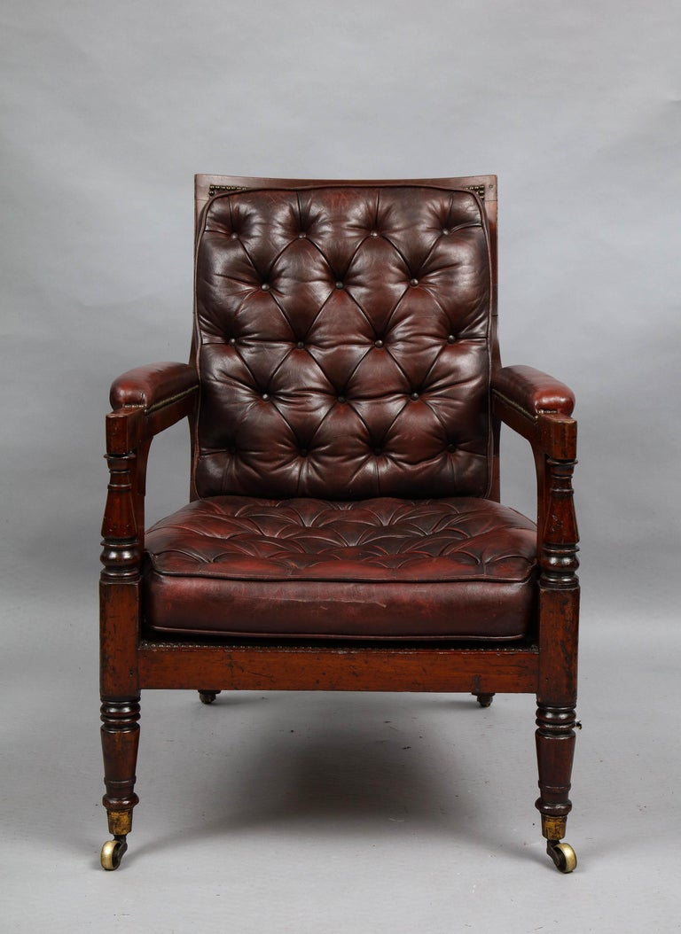 Good early 19th century mahogany library chair of good size and proportion having burgundy leather upholstery, the back with deep buttoning, while the loose cushion seat has shallow tufts over caned support, the whole with good rich color, the arm