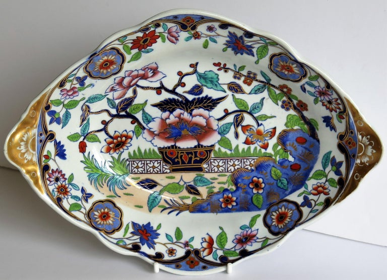 This is a beautiful ironstone dish, bowl or oval plate, produced by the Spode factory, during the late Georgian period, circa 1820.  The dish has an oval shape with fluted sides, a scalloped edge rim and carrying handles formed at either side.  The