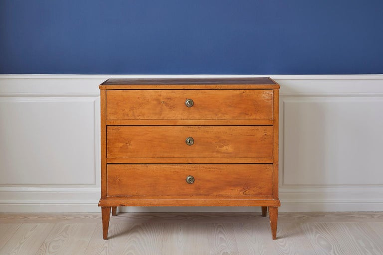 Beautiful Swedish rectangular chest of drawers veneered in birch, in the late Gustavian style. The chest has three drawers including round keyholes in brass and tapered legs.   The vintage chest dates to back to the second half of the 19th