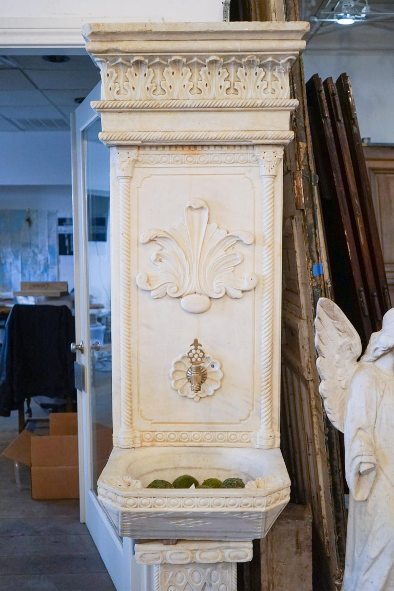 Seated on a carved square pediment, this creamy ivory marble wall fountain features spiral inset columns and molding. A large classical anthemion motif dominates the back splash and repeats atop the cornice. The basin features finely carved