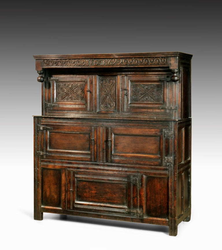 A late 17th century William and Mary period carved oak court cupboard from Westmorland. The court cupboard breaks down into two sections; the upper section has a top rail boldly carved with a scrolling motif and the date 1692 along with the initials